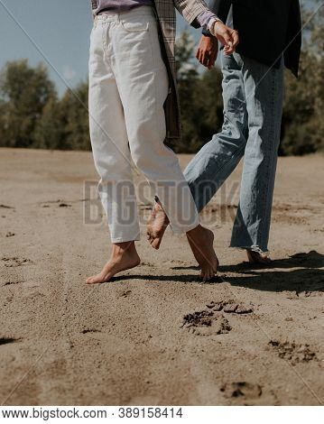 Two Girls Barefoot On The Sand. Girls In White And Blue Pants Are Barefoot On The Sand. Girls Run On