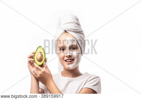 10 Years Old Preteen Chilling Making Clay Facial Mask And Holding Avocado Fruit. Teenage Girl Doing