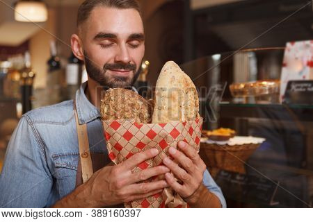 Close Up Of A Handsome Male Baker Smelling Delicious Freshly Baked Bread, Copy Space