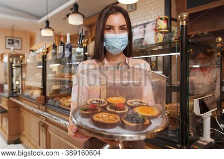 Female Baker Wearing Medical Face Mask, Carrying Tray With Desserts Working At Her Bakery During Cov