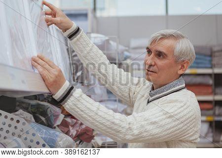 Senior Man Shopping For Bedding At Furnishings Store. Cheerful Elderly Man Enjoying Linen Sales At H