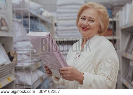 Charming Senior Woman Smiling To The Camera, Shopping For Home Goods At Furnishings Store, Copy Spac