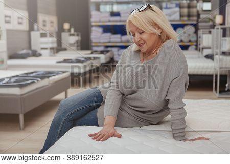 Charming Mature Woman Sitting On Orthopedic Mattress At Furniture Store. Happy Female Customer Choos