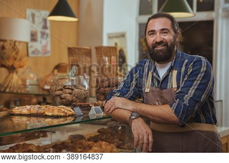 Handsome Mature Bearded Male Baker Smiling To The Camera Proudly, Working At His Bakery Shop, Copy S