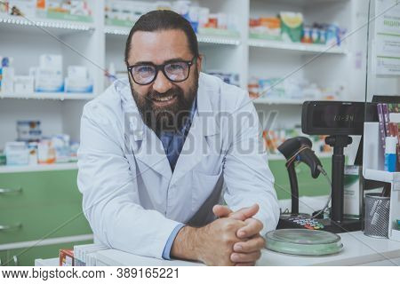 Cheerful Friendly Pharmacist Leaning On A Checkout Counter At His Drugstore, Smiling To The Camera.