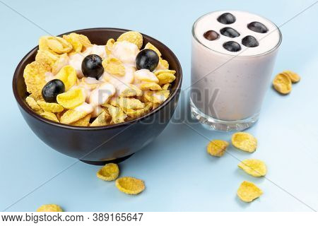 Flakes In A Brown Clay Plate Covered With Yogurt And A Glass Of Yogurt With Grapes On A Blue Backgro