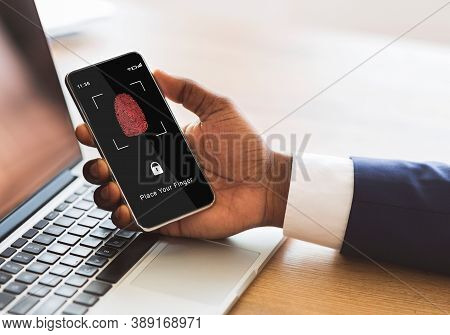 Biometric Identification Concept. African American Man Holding Cellphone In Hand, Showing Applicatio
