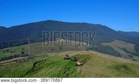 Topview Of Meadow In Mountains With Atv On It. Quad Bikes On The Green Grass.