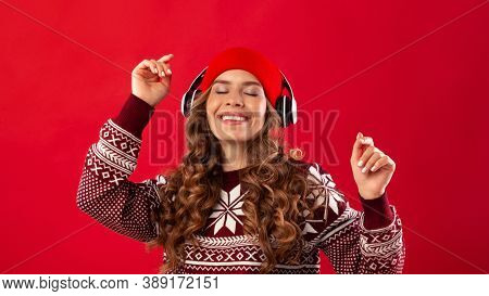 Christmas Music. Pretty Young Woman In Headphones And Winter Outfit Dancing To Her Favorite Song On