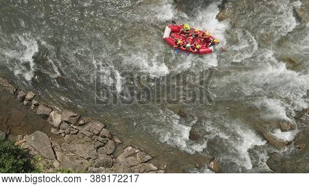 Topview Of People In Yellow Helmets In The Boat. White Waves Of River Water.