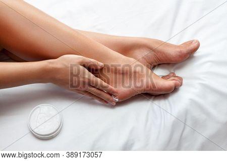 Woman Enjoying A Feet Massage In A Spa. Close Up Of Feet. Woman Hands Giving A Foot Massage. Traditi