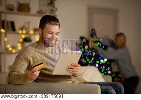 Handsome Smiling Man Shopping Online On Xmas, Using Credit Card And Digital Tablet, Sitting On Sofa