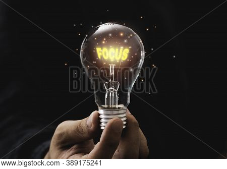 Focus Objective Target Concept,hand Holding Lightbulb Which Contain Illuminating Yellow Focus Wordin