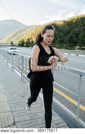 Hasty Woman Running On A Sidewalk With Steel Rail Barrier Along Mountain Highway