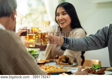 Happy asian multigenerational family of dad mom daughter girl and grandfather cheers together during lunch meal together with joyful. Happy family engagement togetherness concept. Close up at hand.
