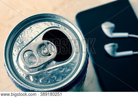 Open Cold Beer Can With Water Drops Near Smartphone And Earphones. Drinking On The Go Beverages In A
