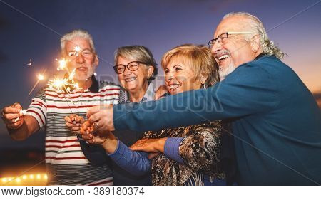 Happy Senior Family Celebrating With Sparkler Fireworks At Home Party - Elderly People Lifestyle And