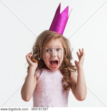 Little cute surprised girl in pink halloween princess costume and crown isolated on white background
