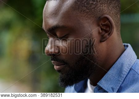 Close Up Portrait Of Serious African American Man With Closed Eyes. Handsome Young Calm Man In Blue