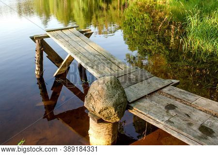 Wooden Bridge On The Shore Of Quiet Forest Lake Is Reflected In Calm Water, Horizontal Photo Of A Su