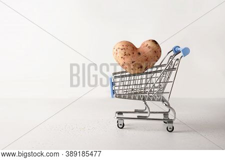 Organic Potato In Shape Of Heart Flying Into Grocery Cart On White Background. Concept Love Homegrow