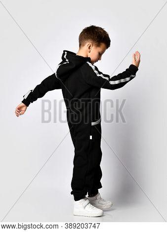 Handsome Boy Wearing Black Warm Sport Jumpsuit In Motion Full Length Studio Shot. Schoolboy Turning