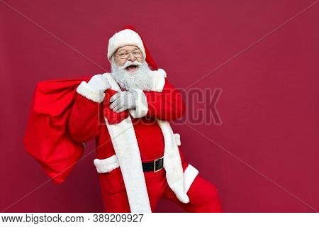Happy Old Funny Santa Claus, Saint Nicholas Wearing Costume Holding Sack Bag With Merry Christmas Pr