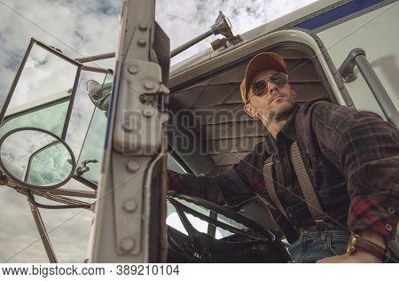 Professional Caucasian Trucker Driver In His 40s In Semi Truck Cabin Enjoying Rest Area Break. Trans