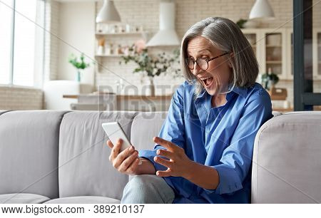 Amazed Happy Mature Older 60s Woman, Excited Customer Holding Smartphone Using Mobile App Feeling Gr