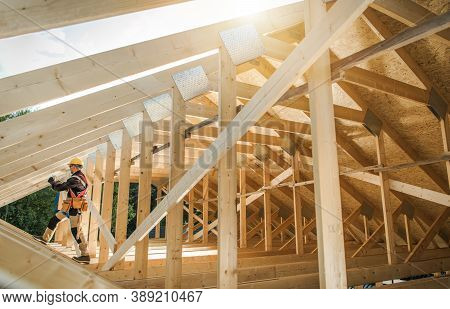 Construction Contractor Worker Building Wooden Roof Skeleton Frame Of The Building. Industrial Theme