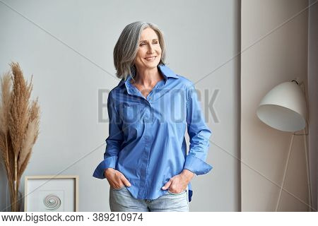 Smiling Confident Mature Woman Standing Indoors Looking At Window. Stylish Elegant Middle Aged Senio