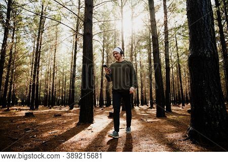 Young Caucasian Male Playing Music From Smartphone Listening Wearing Headphones In Luscious Woodland