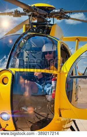 helicopter pilot in the cockpit preparing to take off