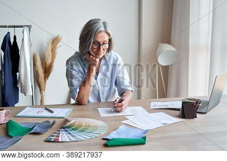 Senior Mature Elegant Female Fashion Designer Drawing Sketches In Studio Office. Middle Aged Stylish