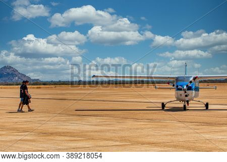 two men walking on the runway to board a small plane used to transport tourists in safari destinations in Botswana, Okavango Delta