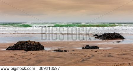 Beautiful Golden Cloudy Sunset Over Layers Of An Incoming Tide And Ridge Of Large Stones On The Down