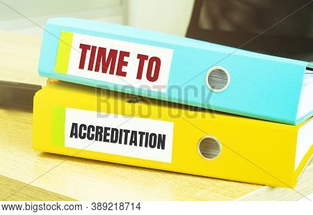 Two Office Folders With Text Time To Accreditation