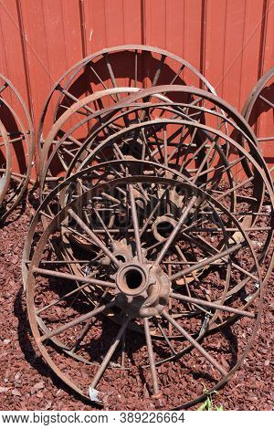 A Collection Of Steel Spoked Wheels Leaning Against The Side Of A Red Barn