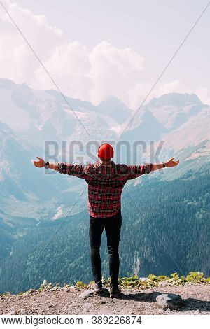 Back View Of A Man Standing Against The Background Of Mountains With His Arms Outstretched. The Man