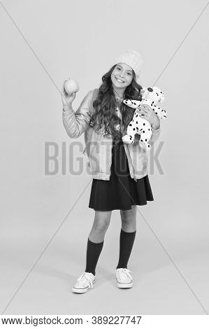 Childhood Games Kid Plays. Happy Girl Hold Toy And Apple. Healthy School Snack. Happy Childhood. Chi