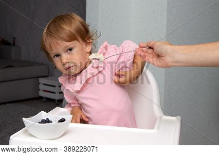 Mother Feeds The Baby Girl With A Spoon. The Two-year-old Child Is Naughty And Refuses To Eat. Cute