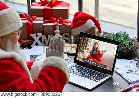 Over Shoulder View Of Santa Claus Video Calling Kid Girl On Laptop Greeting Child By Webcam Talk Ope