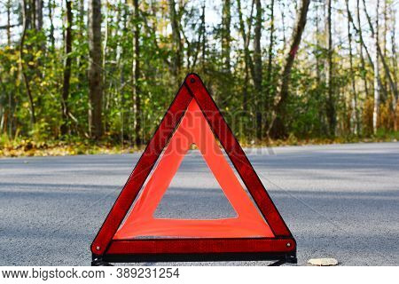 Emergency Stop Sign On The Background Of The Road And Forest. Concept Of Roadside Assistance, Travel