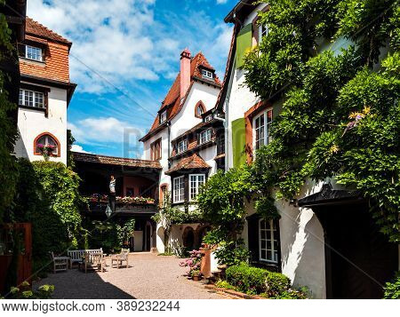 Alsace's Sun-drenched Gingerbread Houses. Tiled Roofs, Flowers All Around, The Summer Sun Is Shining