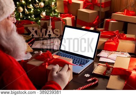 Over Shoulder View Of Santa Claus Holding Xmas Gift Using Laptop Computer With White Blank Empty Moc