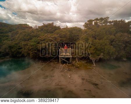 Young Woman On Lookout Platform Admiring The Big Hot Pool In Kuirau Park. Rotorua, New Zealand