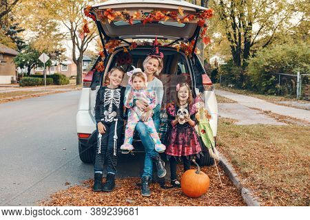 Trick Or Trunk. Family Celebrating Halloween In Trunk Of Car. Mother With Three Children Kids Celebr