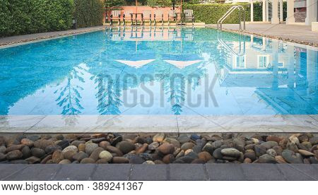Swimming Pool Or Paddling Pool. Consist Of Clean Water, Ladder, Tile Floor, Chair And Empty Space In