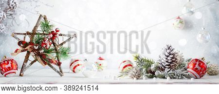 Christmas still life with decorated wooden Christmas Star, pine cone and baubles on light background. Winter festive concept.