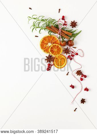Christmas composition with dried oranges and spices on white background. Natural food ingredient for cooking or Christmas decor for home. Flat lay, copy space.